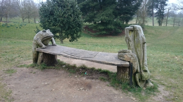This memorial is a carving of a frog and a shovel at either end of a bench with playing cards engraved on it.